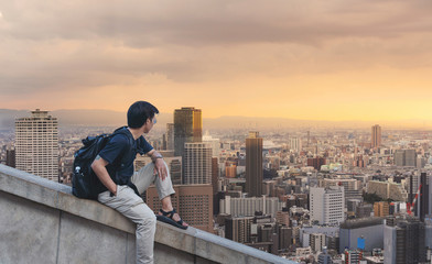 Wall Mural - a man with backpack looking at city skyline view in sunrise