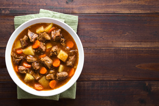 Fresh homemade beef stew with carrot and potatoes served in bowl, photographed overhead with copy space on the side