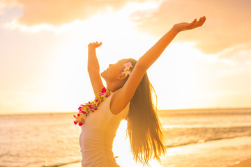 Wall Mural - Hawaii hula dancer woman wearing flower necklace lei on sunset beach dancing with open arms free in sunset relaxing on hawaiian travel vacation. Asian girl with fresh flowers hair, traditional dance.