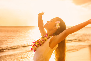 Wall Mural - Hawaii beach sunset Asian woman in sun glow sunset with arms outstretched up dancing in hula luau party enjoying hawaiian vacation