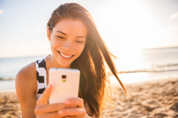 Wall Mural - Smiling Asian woman using phone mobile app on Hawaii beach summer vacation travel holiday. Young tourist lifestyle girl happy texting or taking selfie with cellphone smart phone.