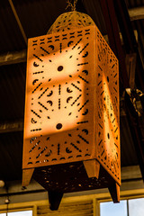 A large rust colored metal lantern hanging by a chain from a shed roof.
