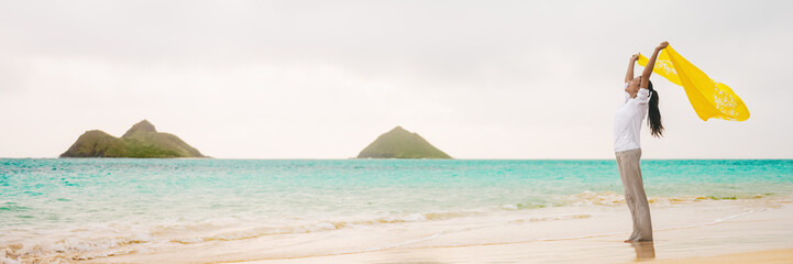 Wall Mural - Wellness happiness freedom woman waving yellow scarf in wind on Hawaii beach banner panoramic background. Serenity peace joy concept.