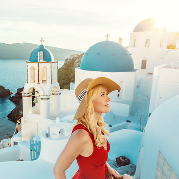 blond woman wearing a red summer dress and a sun hat, with the famous blue church domes in the background, in Oia on Santorini