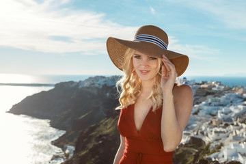 blond woman in a red dress and a sun hat and Oia on Santorini in the background, including the caldera