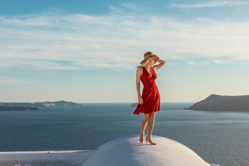blond woman in a red dress and a sun hat, in Oia on Santorini, standing on a roof, with the caldera and aegean sea in the background