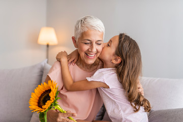 Happy grandmother hugging small cute grandchild thanking for flowers presented, excited granny embrace granddaughter congratulating her with birthday, making surprise presenting bouquet