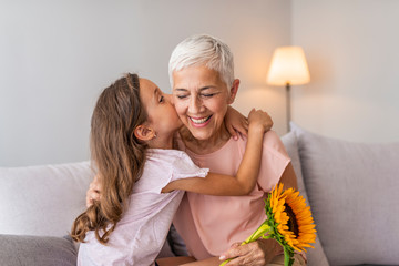 Happy senior grandma hugging granddaughter thanking for gift and flowers. Little granddaughter kissing giving flowers bouquet congratulating smiling old grandmother