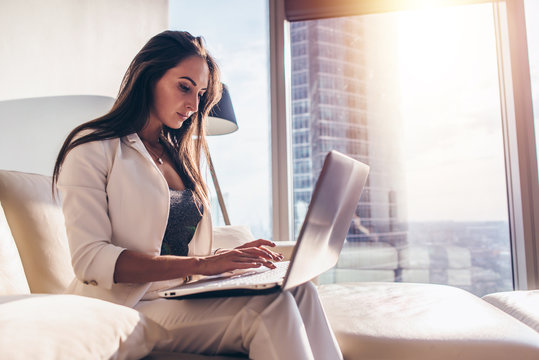 Side view of young woman working on laptop
