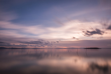 Beautiful long exposure view of Trasimeno Lake (Umbria, Italy), with still water and warm coloured sky