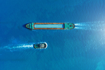 Cargo ship barge and tugboat sail to meet each other in the seaport of the port, aerial view. - fototapety na wymiar