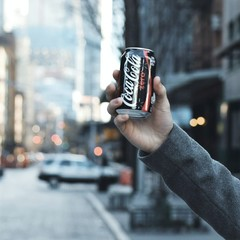coke zero can being held in urban setting