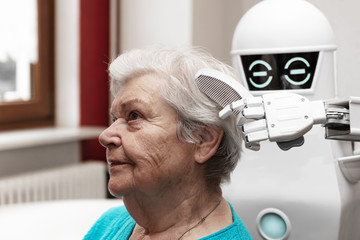 a robotic caregiver is combing the hair of a female senior adult