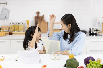 Happy Asian family Mother and Little girl are eating breakfast, cereal  with milk, Bread with jam and see digital tablet in the kitchen at home. Healthy food and Morning activities