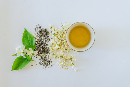 Cup of tea, green tea, dried blossoms of jasmine and sprig of jasmine on white background. Flat lay with copyspace