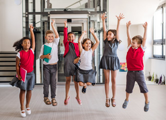 A group of cheerful small school kids in corridor, jumping.