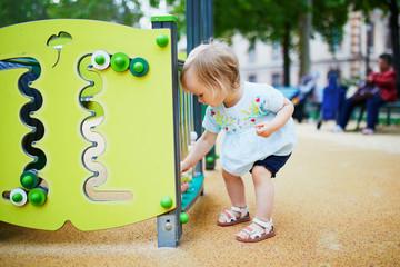 Adorable toddler girl having fun on playground