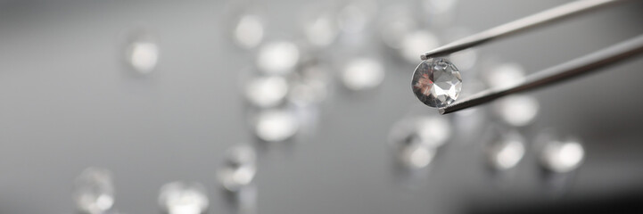 The jeweler holds a diamond in tweezers on a gray background. Selling gems concept.