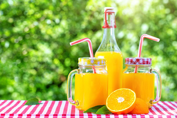 Bottle and cans of mason with orange juice on green natural background