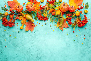 Foto op Aluminium Herfst Autumn concept with pumpkins, flowers, autumn leaves and rowan berries on a turquoise background. Festive autumn decor, flat lay with copy space.