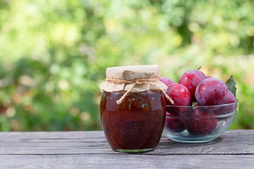 Jar of plum jam with plums on wooden table