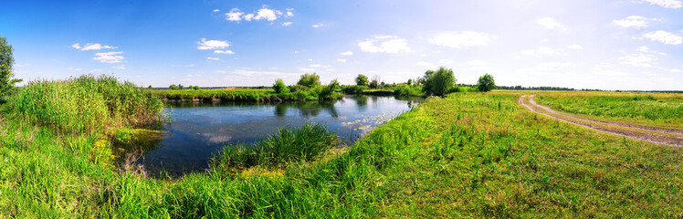 Meadow with river and country road under blue sky