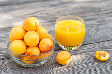 Yellow apricots in glass bowl and juice on wooden table