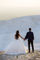 Young wedding couple stands over cliff holding hands and looks into the distance