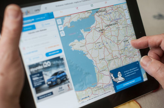 Mulhouse - France - 16 March 2018 - closeup of woman hands on home page of the Michelin map route web site on tablet
