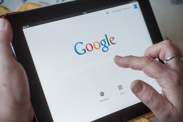 closeup of woman hands on Google home page search of web site on tablet