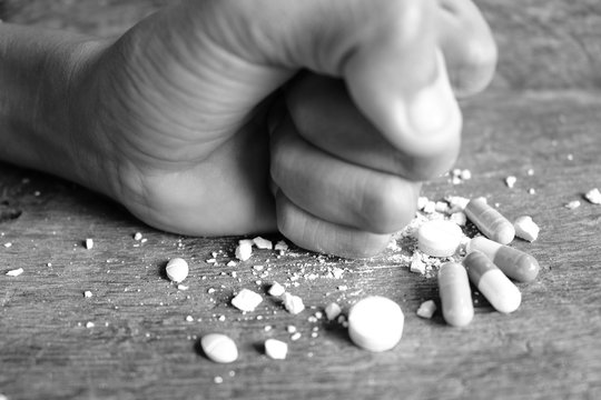 Hands clenched on a multicolored drug placed on a wooden table