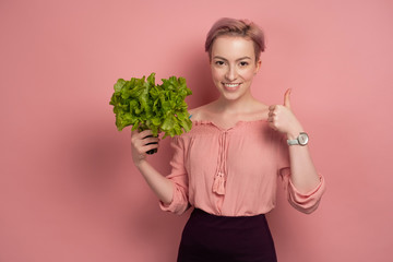 A girl with short pink hair smiling joyfully, looking at the camera, holding a salad and showing a thumb, on a pink background.