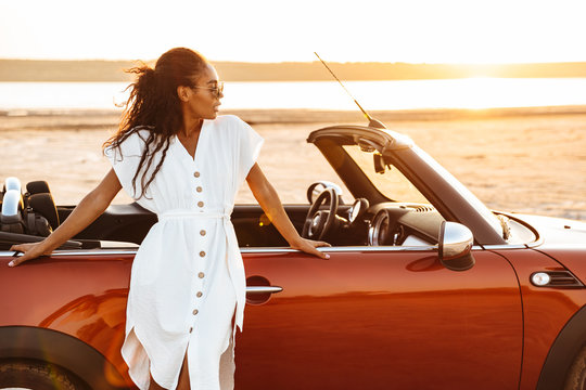 Photo of gorgeous african american woman standing by car on beach at sunrise