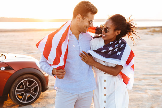 Photo of stylish multiethnic couple smiling and holding american flag while standing by car outdoors