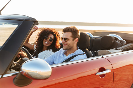Beautiful young multiethnic couple riding in a convertible