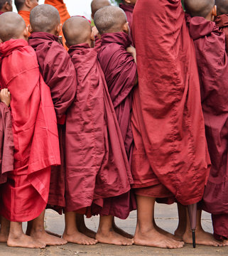 young buddhist pilgrims dressed in red traditional robes waiting to receive merit in myammar