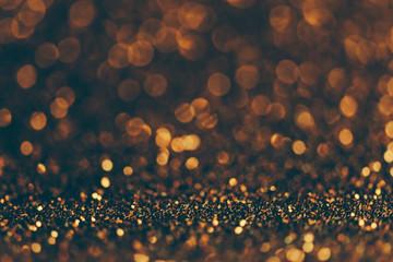 Blur neon gold light circle background. Sparkling firework bokeh dots in retro film filter style.