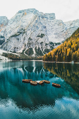 Autumn landscape of Lago di Braies Lake in italian Dolomites mountains in northern Italy. Drone aerial photo with Wooden boats and beautiful reflection in calm water at sunrise. Pragser Wildsee