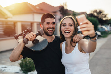 young modern couple walking embraced holding skateboard and taking picture with smartphone