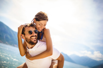 Handsome young man giving piggyback ride to girlfriend on beach. Romantic young couple enjoying summer holidays.
