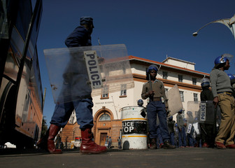 Riot police officers keep watch outside the Tredgold Building Magistrate court in Bulawayo