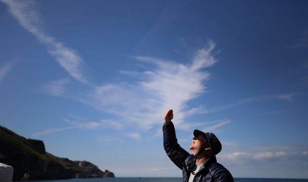 A member of the Cloud Appreciation Society looks up at the sky during a boat trip around Lundy