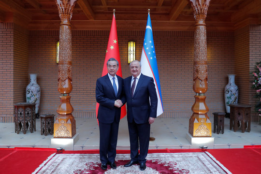 Uzbek Foreign Minister Abdulaziz Kamilov shakes hands with Chinese Foreign Minister Wang Yi during the opening ceremony of the new embassy of Uzbekistan in Beijing