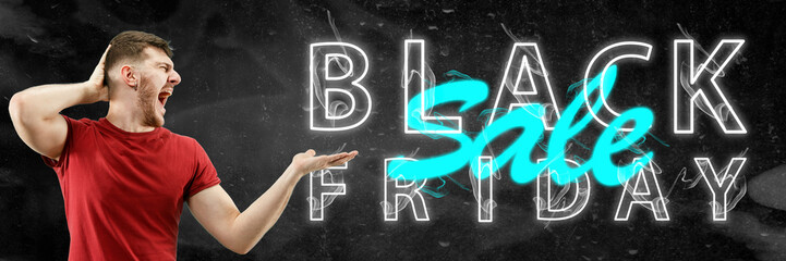 Black friday, sales concept. Neon lighted letters on black background. Astonished man pointing on. Negative space. Modern design. Contemporary art. Creative conceptual and colorful collage.
