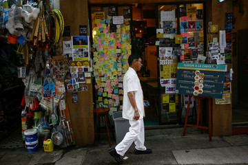 A man walks past a fast-food restaurant that is decorated with sticky notes in support of the anti-government protest movement in the Sheung Wan neighbourhood in Hong Kong