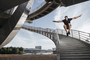 Parkour athlete doing a beautiful high jump from the stairs