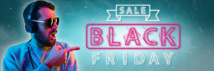 Black friday, sales, purchases concept. Neon lighted letters on gradient background. Astonished man...