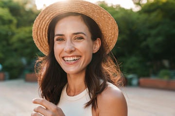 Image of beautiful middle-aged woman laughing and looking at camera while walking in summer park