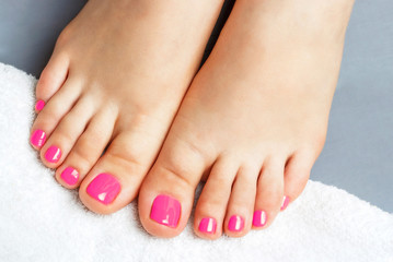 Fotorolgordijn Pedicure Pink pedicure close-up, isolated on a gray background, top view