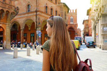 Back view of attractive young woman walking in old medieval town of Bologna, Italy.